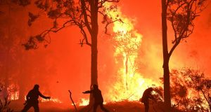 Firefighters work to contain a fire as it encroaches on properties near Termeil, New South Wales, on Tuesday. Photograph: Dean Lewins/EPA