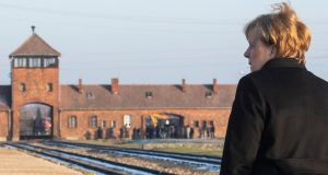 German chancellor Angela Merkel walks past the main railway entrance at the Birkenau camp as she visits the former Nazi death camp Auschwitz-Birkenau in Oswiecim, Poland on December 6th. Photograph: John MacDougall/AFP via Getty