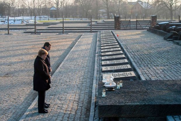 German chancellor Angela Merkel and Polish prime minister Mateusz Morawiecki pay their respects after placing candles at the International Monument Auschwitz II-Birkenau during their visit tot he site. Photograph: John MacDougall/AFP via Getty