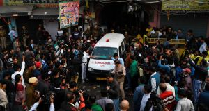 An ambulance surrounded by media drives out from a street leading to the factory site. Photograph: Sajjad Hussain/AFP/Getty Images