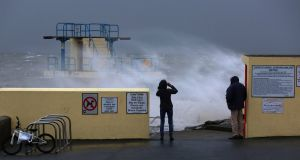 Walkers look out to sea at Blackrock in Salthill, Galway on Sunday as Storm Atiyah arrived. Photograph: Joe O'Shaughnessy