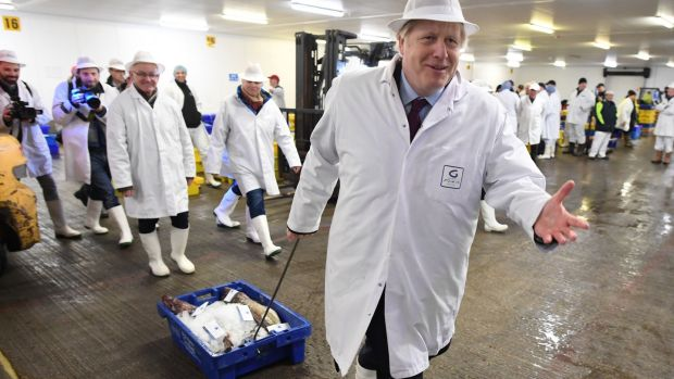 Prime minister Boris Johnson drags a crate of fish during a visit to Grimsby Fish Market, while on the general election campaign trail. Photograph: Stefan Rousseau/PA Wire