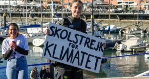 Thunberg shows the placard 'School strike for the climate' upon her arrival in in Lisbon on December 3rd after crossing the Atlantic by boat. Photograph: Horacio Villalobos/Getty
