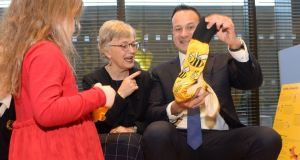 Minister for Children  Katherine Zappone and Taoiseach Leo Varadkar, who was presented with  socks from some children, at the  launch of the national childcare scheme, on Wednesday. Photograph: Dara Mac Dónaill