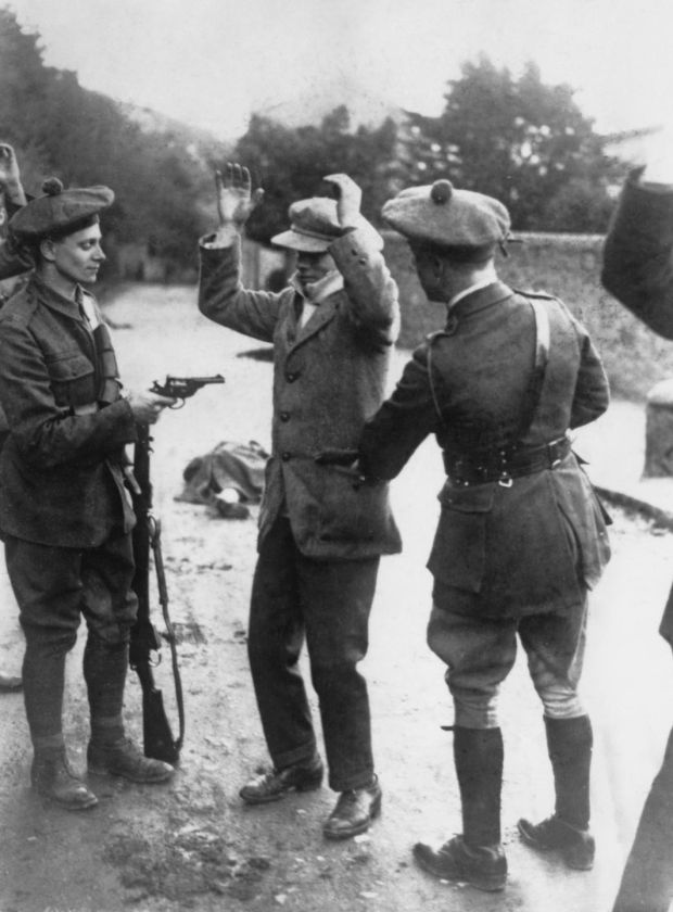 A suspected member of the Irish nationalist party Sinn Féin is searched at gunpoint by temporary constables of the British Black and Tans, during the Irish War of Independence, Ireland, November 1920. Photograph: Topical Press Agency/Hulton Archive/Getty Images