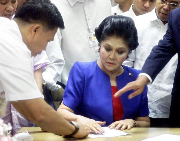 Imelda Marcos being fingerprinted after she surrendered to an anti-corruption court in in Manila in October 2001. Photograph: Erik de Castro/Reuters