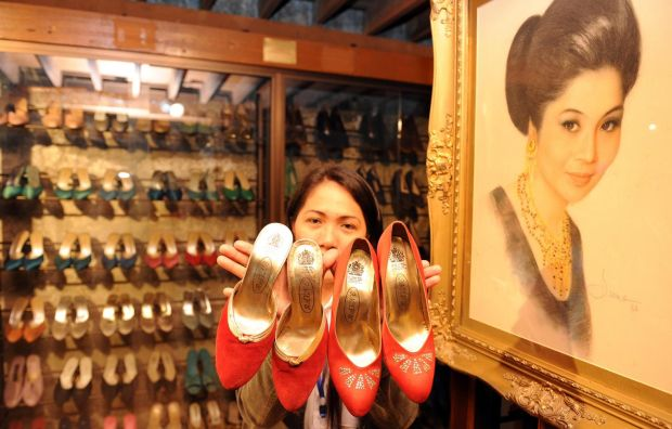 A museum employee displays some of Imelda Marcos's shoes in Manila. Photograph: Ted Aljibe/AFP/GettyImages