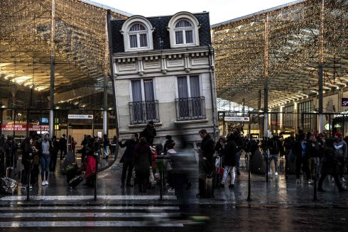 Commuters stand outside Gare du Nord train station and by the piece of art Maison fond (The melting house) by Argentinian artist Leandro Erlich, in Paris, during a strike on Paris's public transport. Photograph: Christophe Archambault/Getty