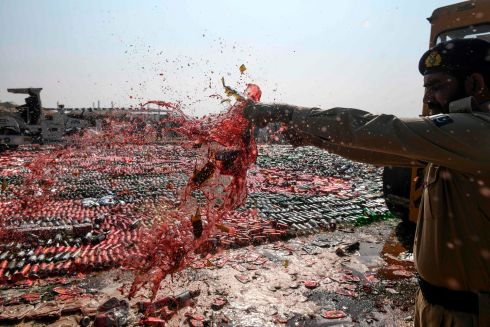 An official destroys seized bottles of liquor, previously smuggled into the country, on the outskirts of Karachi . Photograph: Asif Hassan/Getty