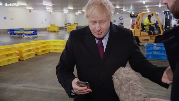 Boris Johnson with ITV reporter Joe Pike. The prime minister refused to look at a photograph of a sick boy and pocketed Pike's phone instead. Photograph: ITV/PA Wire