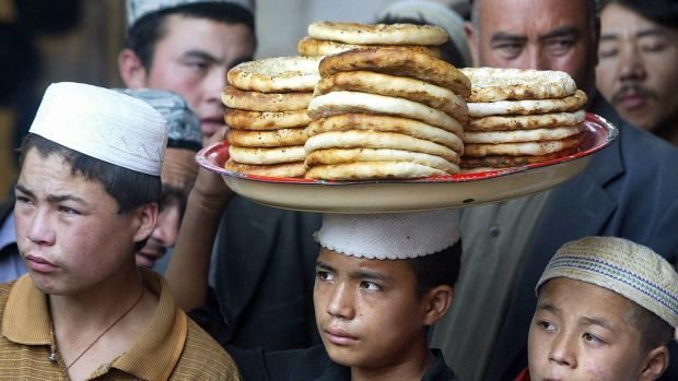 A Uighur boy carries a tray of flat bread for sale in a bazaar in Hotan in China's northwest Xinjiang province. Photograph: Frederic J Brown/AFP/Getty