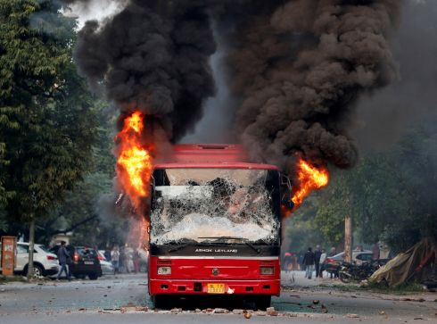 INDIAN PROTESTS: A bus is seen burning after it was set on fire by demonstrators during a protest against a new citizenship law, in New Delhi, India. Photograph: Adnan Abidi/Reuters