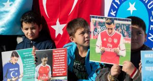 Turkish and Uighur protesters hold pictures of Arsenal's  Mesut Ozil  during a protest against in Istanbul on Saturday. Photograph: Tolga Bozoglu/EPA