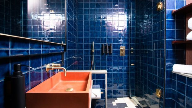 The shower room has dark blue tiles, and ochre-painted concrete wash-basins.