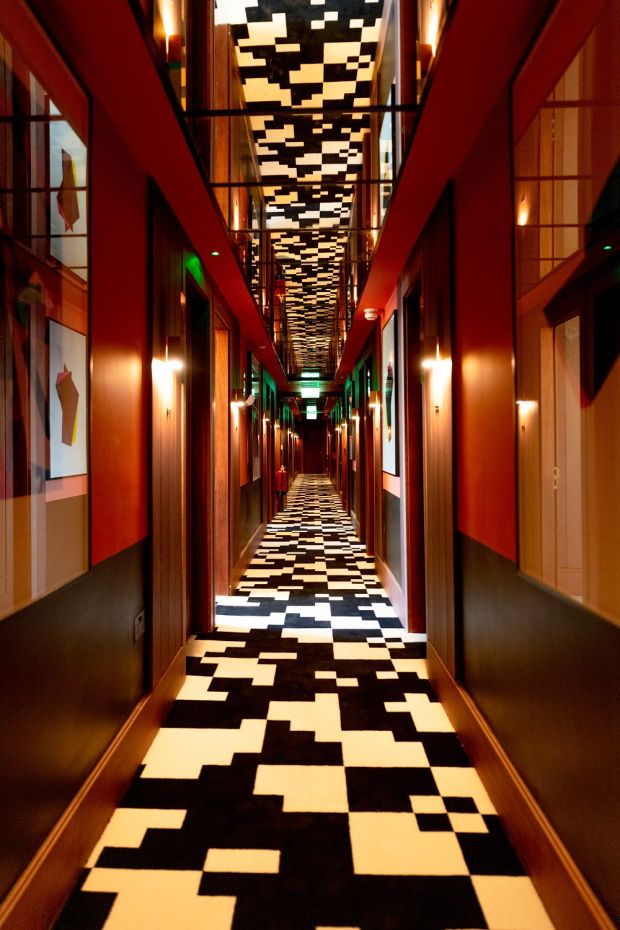 Each of the bedroom floors has a striking corridor of geometric black and white carpet.