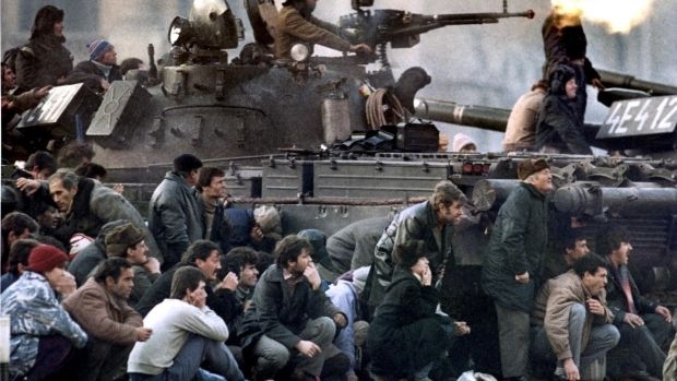 Bucharest residents protect themselves from crossfire between an army tank and pro-Ceausescu troops during clashes in the Republican square in Bucharest on December 23rd, 1989. Photograph: Charles Platiau/Reuters