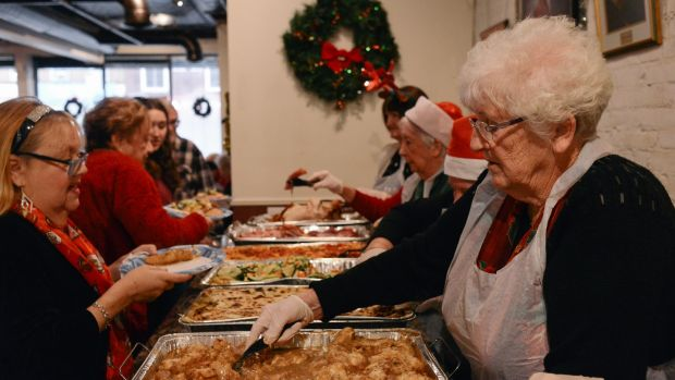 Board member Bridie Mitchell serves Christmas lunch at the New York Irish Center. Photograph: Lauren Crothers