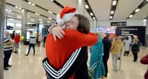 Briain McGeary dressed as Santa embraces his sister Brónagh on her arrival back from Vancouver after one year. Photograph: Alan Betson / The Irish Times