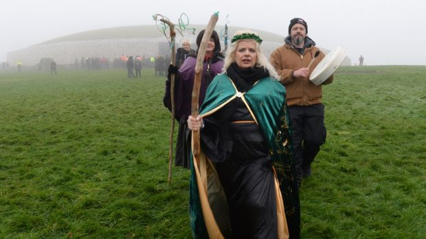 Bridget O'Brien, Ballinagore, Co. Westmeath,leads a group gathered outside the burial chamber at Newgrange in Co, Meath for the winter solstice. Photograph: Dara Mac Dónaill / The Irish Times