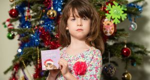 Florence Widdicombe (6) at her home in Tooting, south London, holding a Tesco Christmas card from the same pack as the one which contained a message from a Chinese factory worker. Photograph: Dominic Lipinski/PA Wire