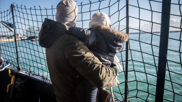 A father holds his baby on the deck of the Alan Kurdi, as the ship pulls into the port of Pozzallo, Italy, on December 29th, 2019. Photograph: Sally Hayden