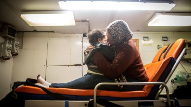A pregnant woman holds her child as the Alan Kurdi pulls into the port of Pozzallo, Italy, on December 29th, 2019. Photograph: Sally Hayden