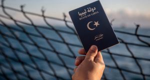 A Libyan man  holds up his Libyan passport on the deck of the Alan Kurdi rescue ship. Photograph: Sally Hayden