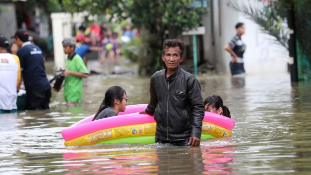 Residents wade through a flooded neighbourhood in Tanggerang on the outskirts of Jakarta, January 2nd, 2020. Photograph: AP Photo/Tatan Syuflana