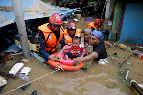 JAKARTA FLOODS: Indonesian rescuers evacuate a boy from a flooded area in Jakarta, Indonesia.  Photograph: Mast Irham/EPA