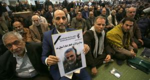 An Iranian man holds a poster of slain Iranian Revolutionary Guard major general Qassem Suleimani during a mourning prayer in Tehran on Friday. Photograph: Atta Kenare/AFP