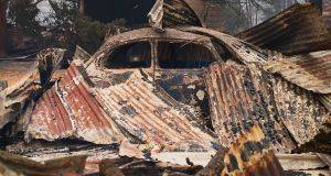The frame of a Volkswagen Beetle is pictured underneath a burnt out structure  in Wingello on Sunday. Photograph: Getty Images