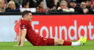 Liverpool's James Milner sits injured  during Sunday's FA Cup third round match against Everton at Anfield. Photograph: Peter Byrne/PA Wire