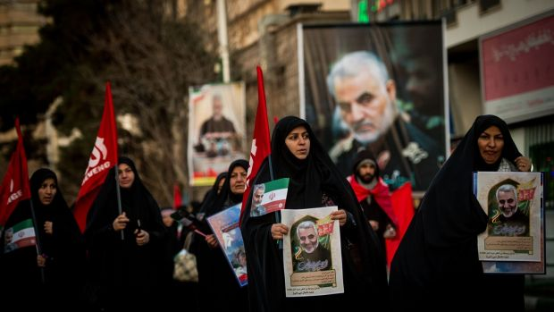 Mourners carry images of Iranian general Qassem Suleimani during the funeral ceremony in Tehran. Photograph: Ali Mohammadi/Bloomberg