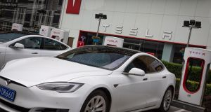 Electric cars from Tesla are charged at a charging station in front of Tesla China headquarters in Beijing.