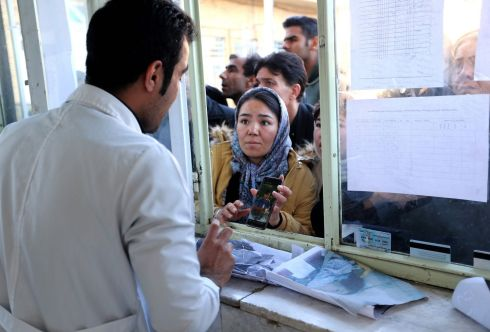 FUNERAL AFTERMATH: An anxious woman shows a medic a picture of her missing brother as people queue to check whether family members are accounted for, outside the information office of a hospital in the Iranian city of Kerman, following a stampede at the funeral of Revolutionary Guards commander Qasem Suleimani on Tuesday. The crush killed scores of people. Photograph: Atta Kenare/AFP/Getty