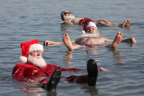 CALM AFTER THE STORM: Tourists wearing various amounts of Santa Claus clothing float in the salty waters of the Dead Sea at Neve Midbar beach in Israel. Photograph: Abir Sultan/EPA