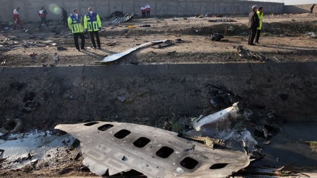 Officials stand near the wreckage after an Ukraine International Airlines Boeing 737-800 carrying 176 people crashed near Imam Khomeini Airport in Tehran, killing everyone on board; in Shahriar, Iran. photograph: Abedin Taherkenareh/EPA