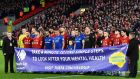 Everton and Liverpool players pose with a mental health banner before their FA Cup third round match at Anfield. Photograph: Getty Images