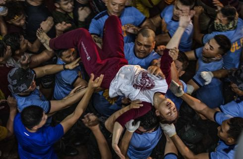 CATHOLIC PROCESSION: A Catholic devotee is carried away after fainting while taking part in the annual procession of the Black Nazarene in Manila, Philippines. Photograph: Ezra Acayan/Getty Images