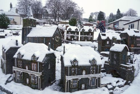 WINTER WONDERLAND: Rawson Robinson, from Nenthead, England, clears snow from the model village he has built in his garden. Photograph: Owen Humphreys/PA Wire