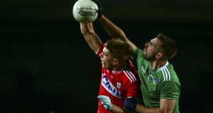 Limerick's Tommy Griffin challenges Cork's Ian Maguire in the air. Photo: Ken Sutton/Inpho