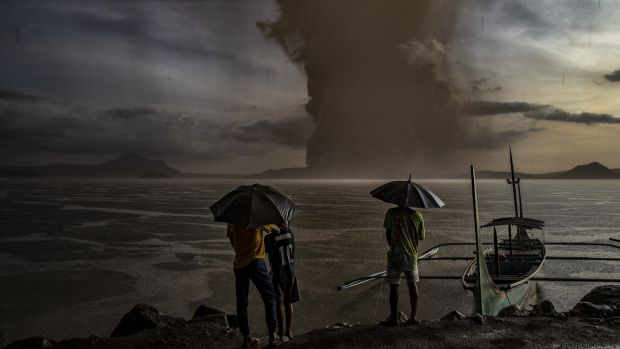 Residents look on as Taal Volcano erupts in Talisay, Batangas province, Philippines Photograph: Ezra Acayan/Getty Images