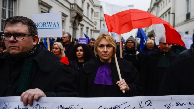 A judge holds a Polish flag during the Thousand Scarlet Robes March. Photograph: Getty