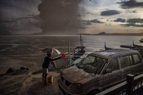 PHILPPINES VOLCANO: A resident tries to clean his car which is covered in ash after Taal Volcano erupted in Talisay, Batangas province, Philippines. Local authorities evacuated residents nearby on Sunday. Photograph: Ezra Acayan/Getty Images