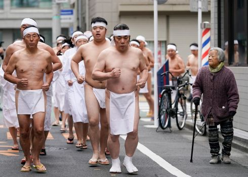 HARDY SOULS: Men wearing only loincloths run to warm themselves up before bathing in ice-cold water during a purification ceremony at the Teppozu Inari Shrine in Tokyo, Japan. Photograph: Christopher Jue/EPA