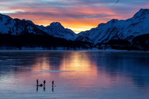 "SWITZERLAND: People out on the Silsersee (lake Sils), covered with so-called ""black ice"", in Sils, Switzerland. Photograph: Gian Ehrenzeller/EPA"