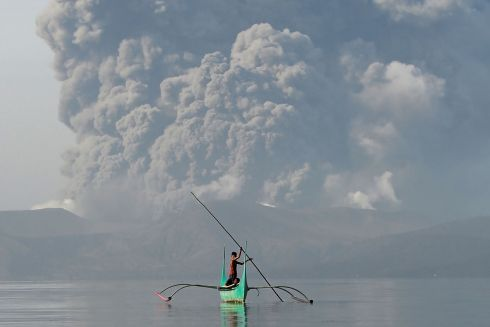 FIRE AND BRIMSTONE: A young man who lives near Taal volcano paddles an outrigger canoe while the volcano spews ash, near Tanauan town in Batangas province, south of Manila. The Philippines has been on high alert after a massive column of ash forced a halt to flights at the capital's main airport. Photograph: Ted Aljibe/AFP/Getty