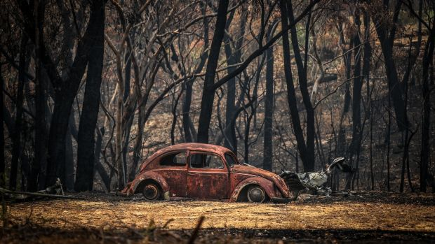 The remains of a car that was destroyed by bushfires sits near a home in the town of Balmoral in Australia. Photograph: David Gray/Getty Images