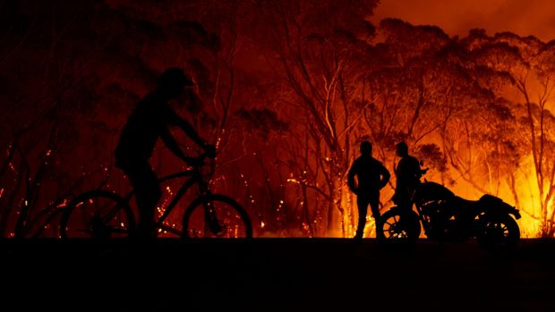 Residents look on as flames burn through bush in Lake Tabourie, Australia. Photograph: Brett Hemmings/Getty Images