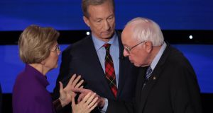Elizabeth Warren and  Bernie Sanders speak as Tom Steyer looks on after the Democratic presidential primary debate at Drake University  in Des Moines, Iowa. Photograph: Scott Olson/Getty Images
